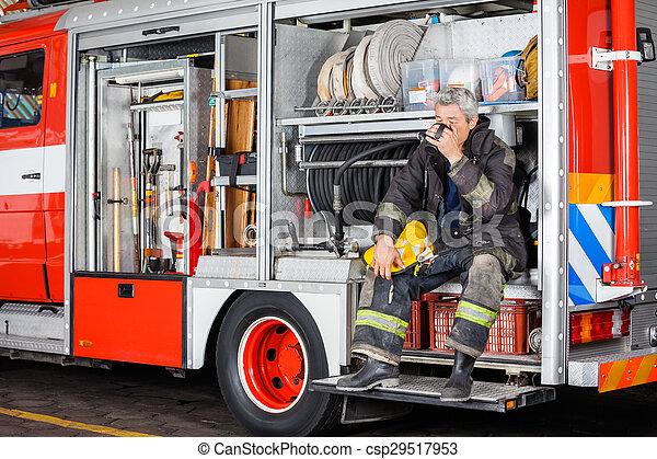 Bombero bebiendo café mientras está sentado en un camión - csp29517953