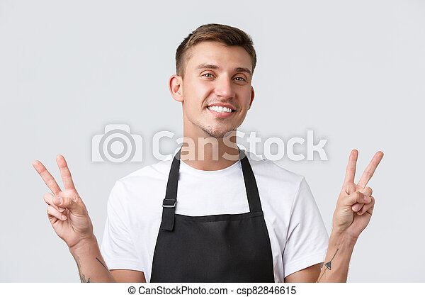 Cafe and restaurants, coffee shop owners and retail concept. Close-up of friendly cheerful barista, waiter in black apron, showing peace sign and smiling broadly, welcome guests, white background - csp82846615