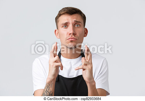 Cafe and restaurants, coffee shop owners and retail concept. Sad hopeful barista, salesman in black apron feel uneasy and nervous, pouting while cross fingers good luck, praying in despair - csp82933684