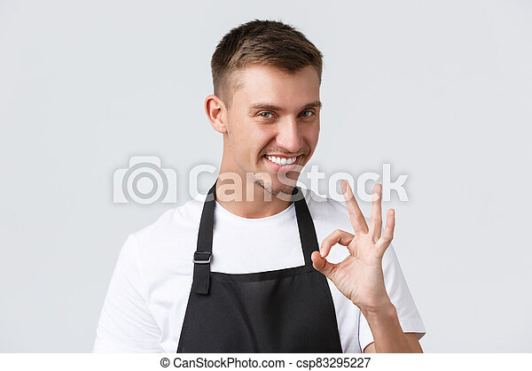 Cafe and restaurants, coffee shop owners and retail concept. Close-up of cheeky handsome waiter in black apron, barista guarantee quality of drinks, showing okay sign and smiling pleased - csp83295227
