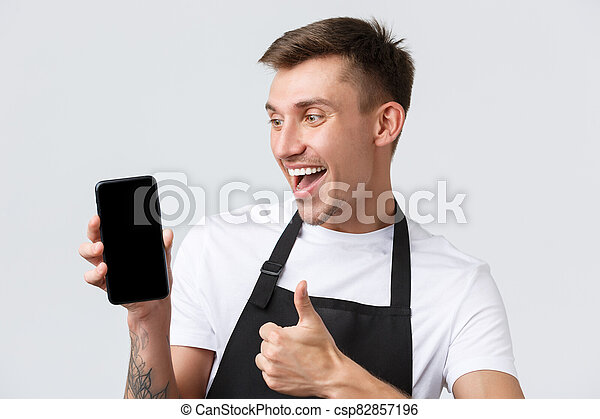 Cafe and restaurants, coffee shop owners and retail concept. Joyful handsome salesman, looking at mobile phone screen impressed, like new app or webpage showing thumbs-up in approval - csp82857196