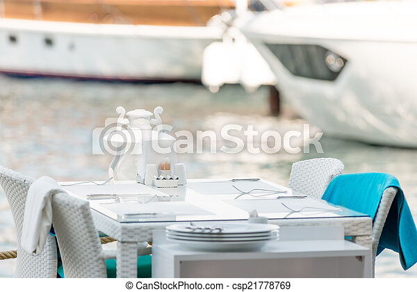 cafe table is located on the pier near the sea - csp21778769