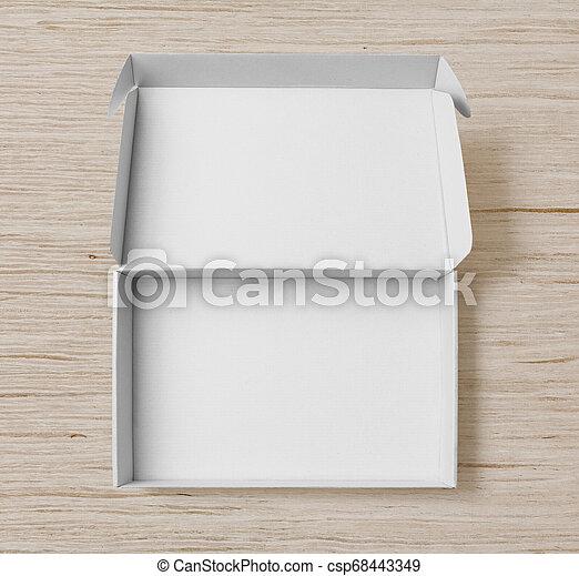 Una caja de cartón blanca de primera vista sobre fondo de madera blanca - csp68443349