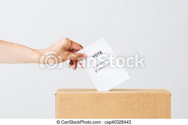 Hombre poniendo su voto en la urna en las elecciones - csp40328443