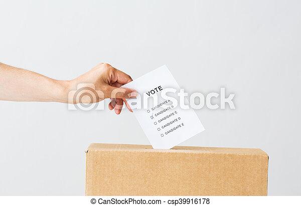 Hombre poniendo su voto en la urna en las elecciones - csp39916178