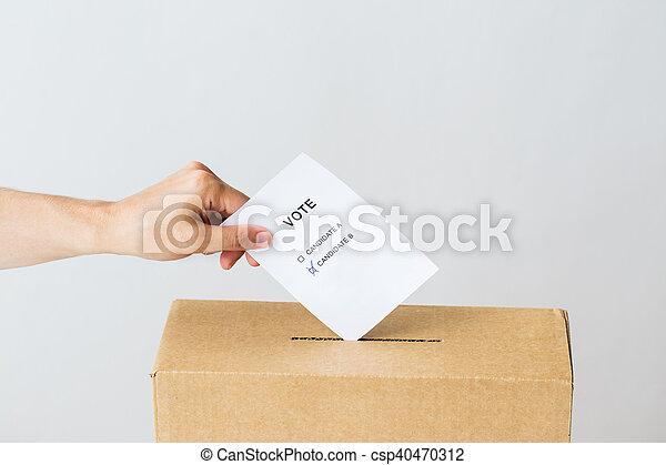 Hombre poniendo su voto en la urna en las elecciones - csp40470312