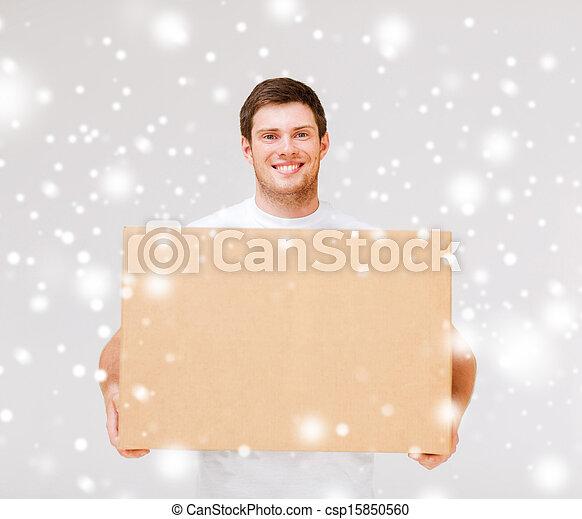 Hombre sonriente llevando caja de cartón - csp15850560