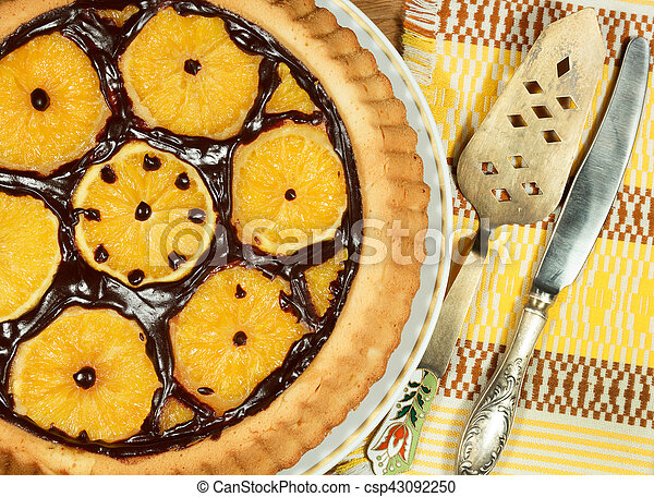 Cake decorated with orange slices on wooden tray. - csp43092250