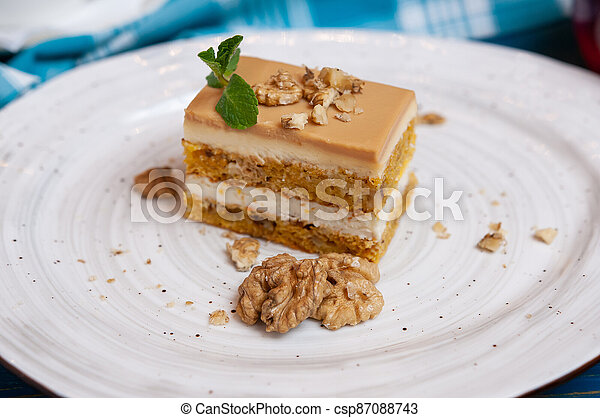 Cake with cream and walnuts on a white plate - csp87088743