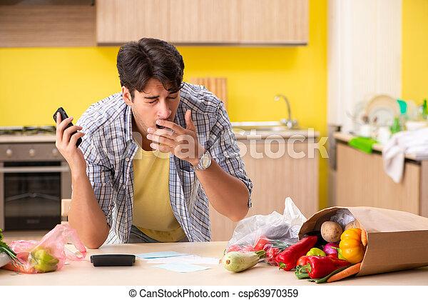 Un joven calculando expensas de verduras en la cocina - csp63970359