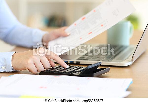 Contable calculando con una calculadora en un escritorio - csp56353527