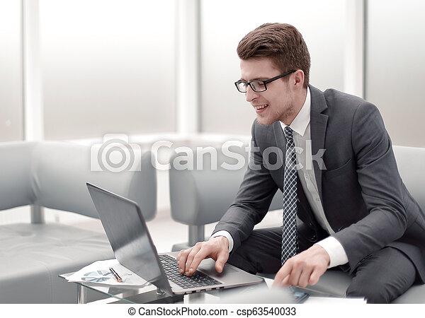 Cerca. Empresario sonriente usando portátil y calculadora. - csp63540033