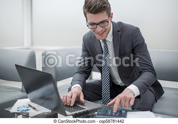 Cerca. Empresario sonriente usando portátil y calculadora. - csp58781442