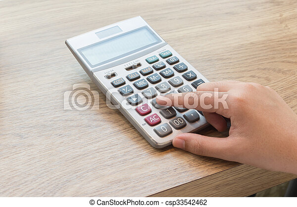 Calculator with hand on wood desk. - csp33542462