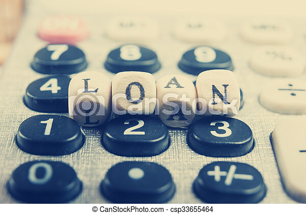 Calculator with the word loan written in wooden block letters - csp33655464
