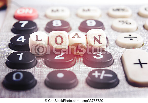 Calculator with the word loan written in wooden block letters - csp33768720