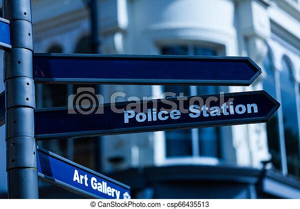 El letrero de la estación de policía colgado en la farola. Señal de flecha con dirección de la estación de policía. - csp66435513