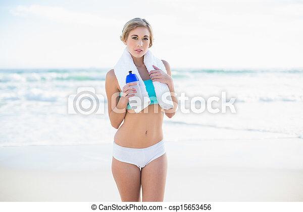 Calm blonde woman in sportswear holding a bottle of water - csp15653456