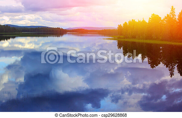 Calm lake reflection against the blue sky with white clouds  - csp29628868
