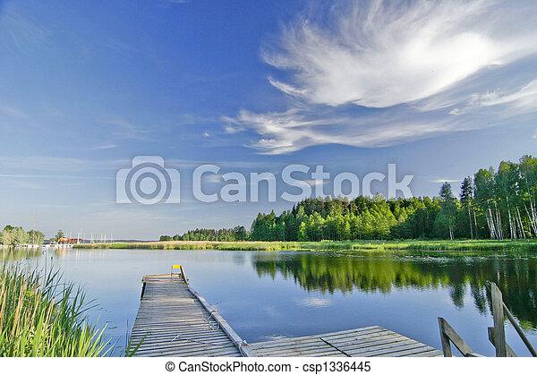 Calm lake under vivid sky in summer - csp1336445