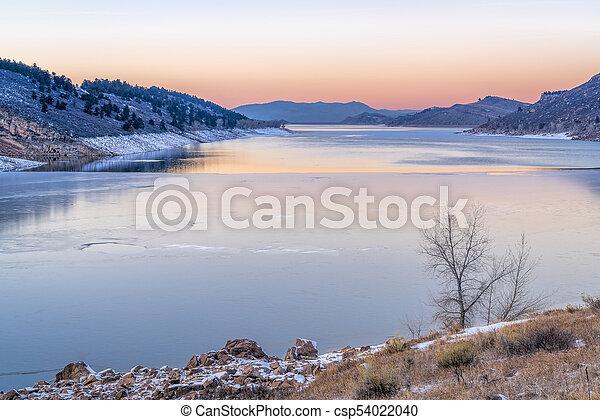 calm winter dusk over mountain lake - csp54022040