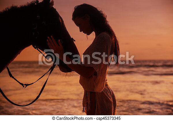 Calm woman cuddling a majestic stallion - csp45373345