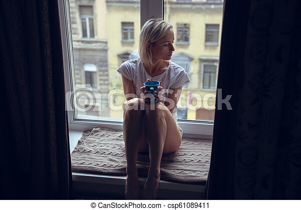 Calm woman with cup of tea or coffee sitting and drinking on the window-sill at home. - csp61089411