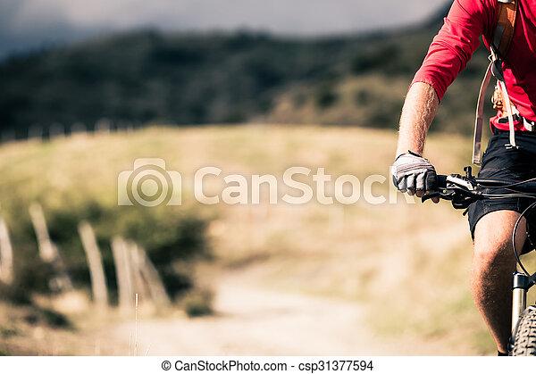 Montador de bicicletas de montaña en la carretera del campo, rastro en paisaje inspirador - csp31377594