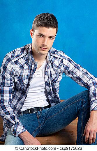 Un joven apuesto con camisa a cuadros sentado en madera - csp9175626