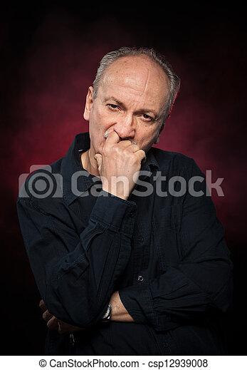 Guapo hombre de último año con camisa negra en el fondo oscuro - csp12939008