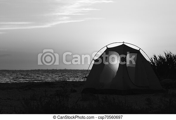 Camping tent on sea beach at sunset in summer - csp70560697