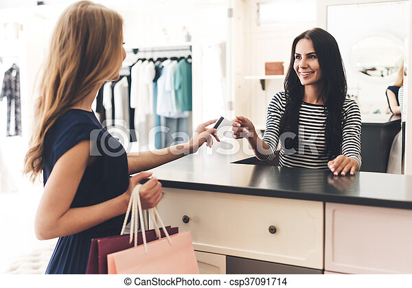 5d83e3830e Can I Pay With My Card? Beautiful Young Woman With Shopping Bags Giving Her  Credit Card To Seller