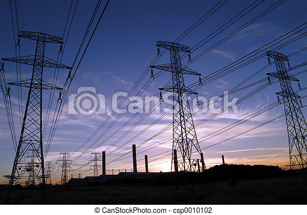 Three high voltage electricity pylons (towers) against background of dark blue and orange sky with industrial chimneys.