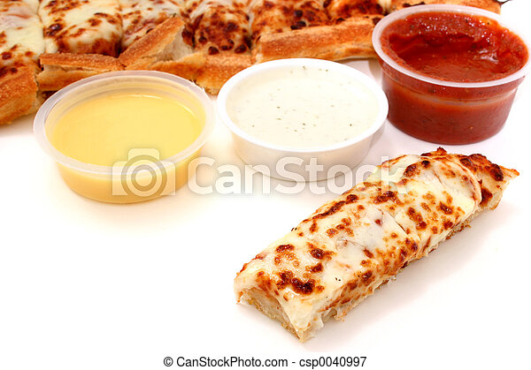 Take cheese pizza sticks with a container of marinara sauce, ranch dressing and garlic butter.  Focus on pizza stick in front. Shot with the Canon 20D. - csp0040997