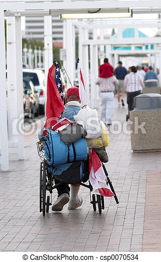 A homeless veteran in a wheelchair with a flag.