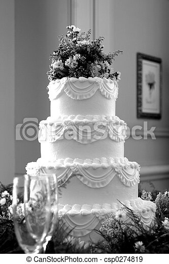 Black and white photo of a beautiful wedding cake with champagne glasses in foreground. Shot with Canon 10D.