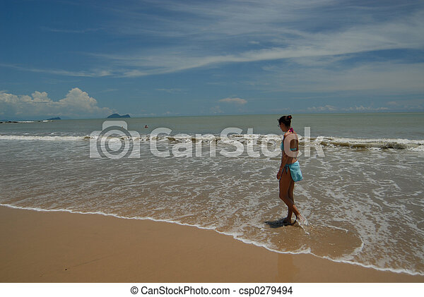 Stock photo of beautiful tall brunette woman on the beach in the tropics - csp0279494