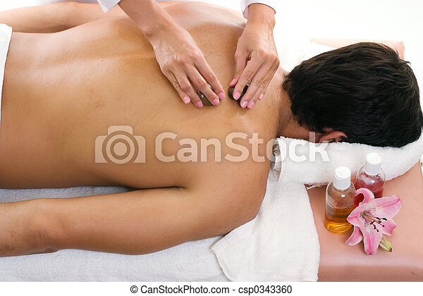 Man receiving thermal stone massage - csp0343360