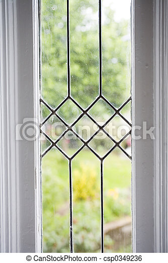 Photo of a leaded glass window with a garden in the background.