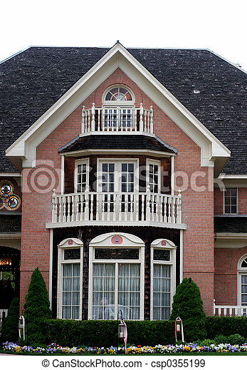 Colonial home with red brick, white trim, and black shingles with beautiful front garden