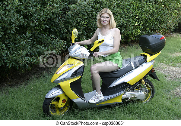 Beautiful Middle Aged Woman Driving a Scooter 2 - csp0383651