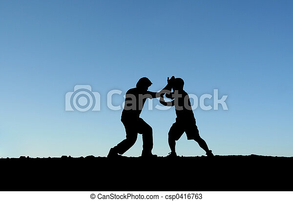 Two men practicing martial arts on top of a mountain (in silhouette)