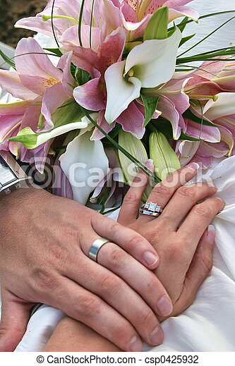 bride and groom holding hands showing rings
