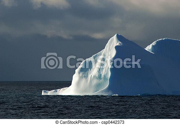 Sunlit white-blue iceberg with dark sky - csp0442373