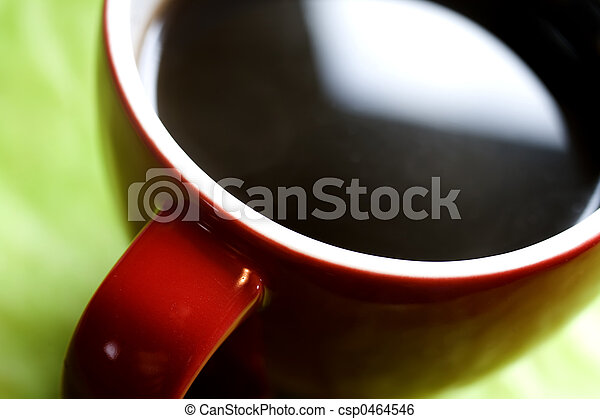 Photo of a red coffee cup on a green background.