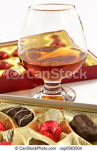Glass with cognac and sweets with liquor  - csp0563504