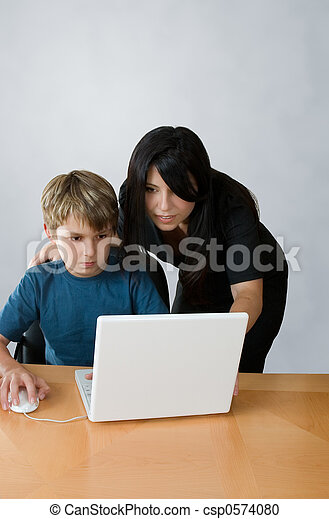 Adult assisting child on computer - csp0574080