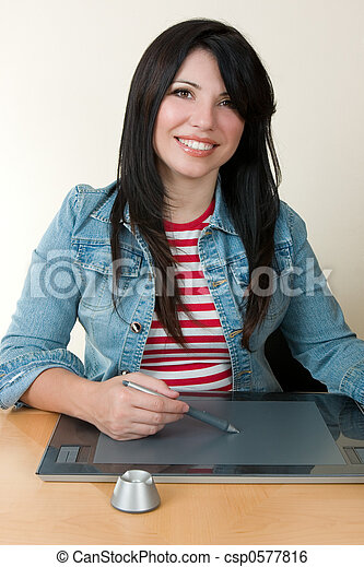 A smiling woman sitting at desk using a graphic tablet