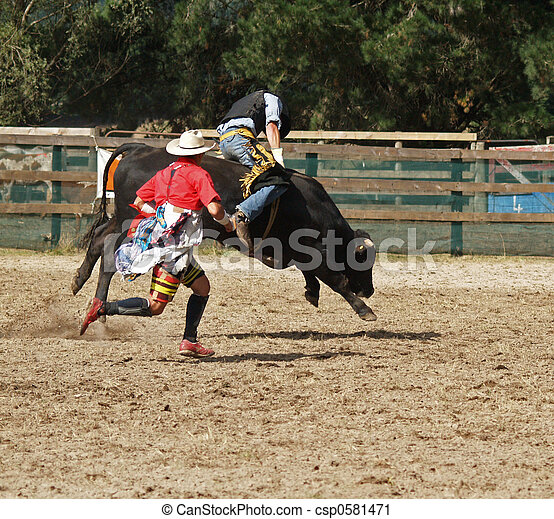 A cowboy riding a steer during a rodeo competition. The rodeo clown is running beside him