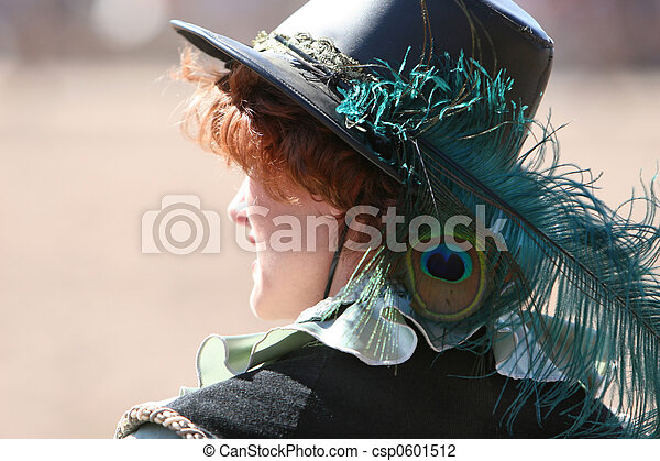 A young woman looking into the distance. She is wearing a old fashioned black leather hat which has a beautiful peacock feather in it. - csp0601512